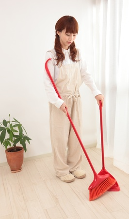 Young Asian woman with a broom to clean up Stock Photo