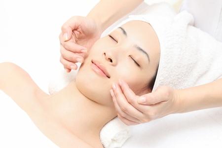 masajes faciales: Mujer joven asiática para hacer frente a masajes Foto de archivo