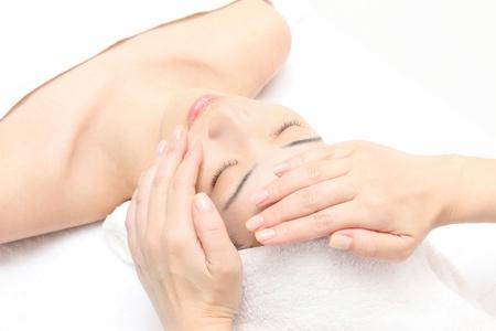gezichtsbehandeling: Jonge Aziatische vrouw te masseren gezicht Stockfoto