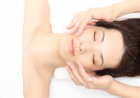 Junge asiatische Frau zu massieren Gesicht