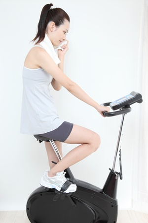 bycicle: Beautiful young Asian woman Indoor bycicle cycling  Stock Photo