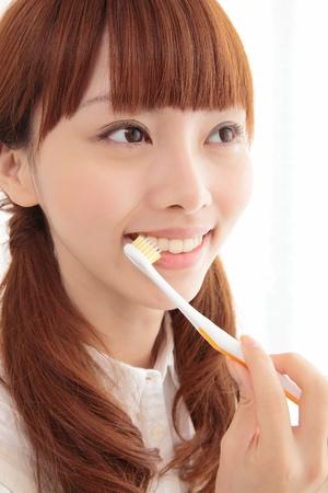 Beautiful young Asian woman brushing photo