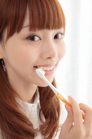 bad breath: Beautiful young Asian woman brushing