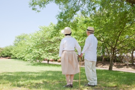 to cuddle: Rear Asian elderly couple take a cane Stock Photo