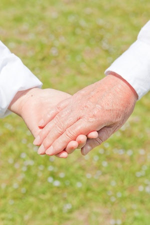 An old couple holding hands photo