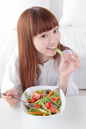 Beautiful young Asian woman to eat vegetables photo