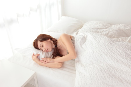 Beautiful young Asian woman sleeping on the bed photo