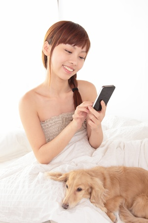 koreans: Women use a cell smart mobile phone on the bed