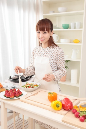 koreans: Beautiful young Asian woman is being prepared to make a salad in the kitchen.