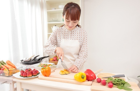 アジア美人 w は台所で料理を準備しています。 写真素材