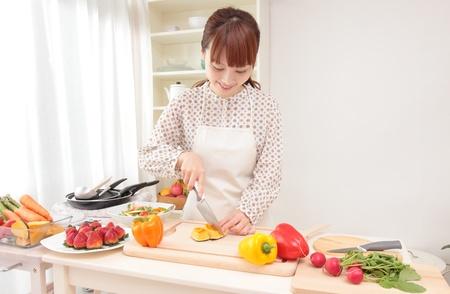 Belle femme asiatique w est en préparation pour la cuisson dans la cuisine.