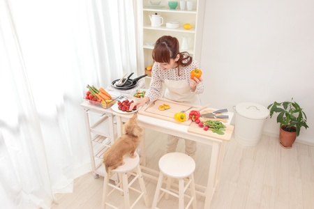 Beautiful Asian women, is being prepared for cooking in the kitchen along with the dog.
