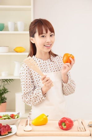 Asian beautiful woman with a smile is in preparation for cooking in the kitchen. photo
