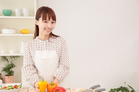 japanese cooking: Asian beautiful woman with a smile is in preparation for cooking in the kitchen.