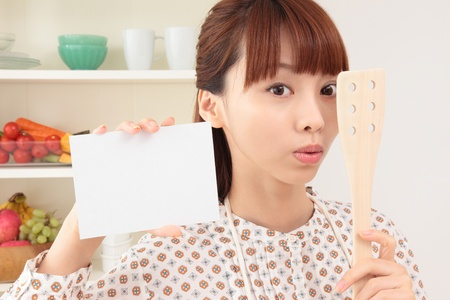 oriental cuisine: Asian woman with an empty card in the kitchen