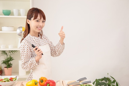 Young Asian woman to make a finger in the kitchen photo