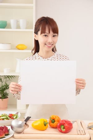 foodie: Asian woman with an empty board in the kitchen