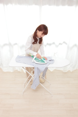 Young Asian woman ironing at the window Stock Photo - 12413375