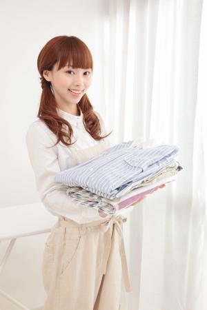洗濯物を持つウィンドウで美しい若いアジアの女性