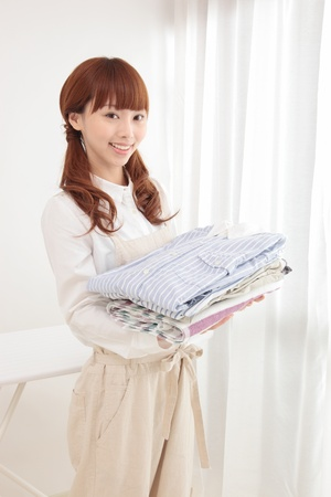 work clothes: Beautiful young Asian woman at the window with the laundry Stock Photo