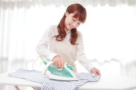 iron curtains: Young Asian woman ironing at the window