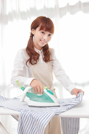 Young Asian woman ironing at the window Stock Photo - 12413379