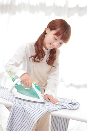 Young Asian woman ironing at the window Stock Photo - 12413380