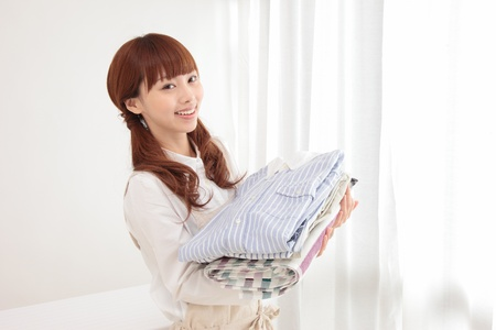laundry room: Beautiful young Asian woman at the window with the laundry Stock Photo