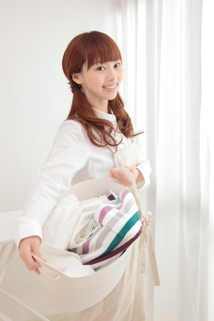 work clothes: Beautiful young Asian woman with a laundry basket at the window