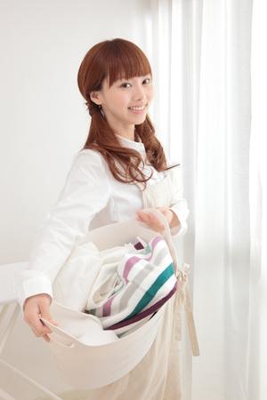 ama de casa: Joven y bella mujer asi�tica con un cesto de la ropa en la ventana