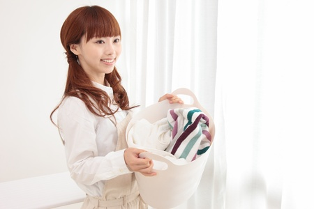 laundry room: Beautiful young Asian woman with a laundry basket at the window