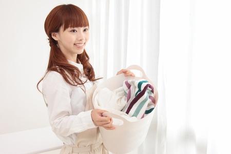 Laundry: Joven y bella mujer asi�tica con un cesto de la ropa en la ventana