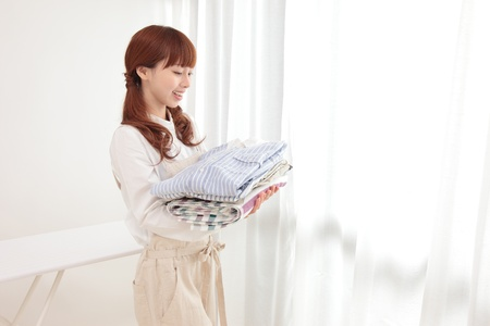 Beautiful young Asian woman at the window with the laundry photo