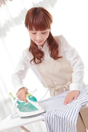 Young Asian woman ironing at the window photo