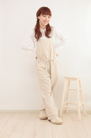 bright housekeeping: Beautiful young Asian woman wearing overalls in a bright room Stock Photo