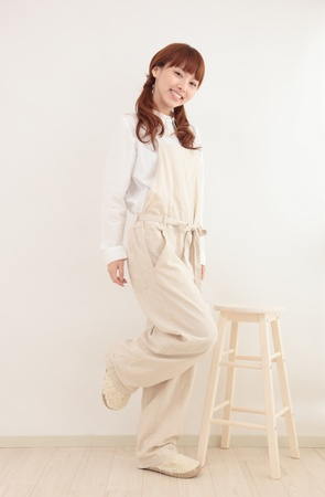 Beautiful young Asian woman wearing overalls in a bright room Stock Photo - 12413384