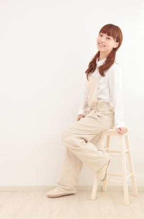 bright housekeeping: Beautiful young Asian woman dressed in overalls sit in a bright room. Stock Photo