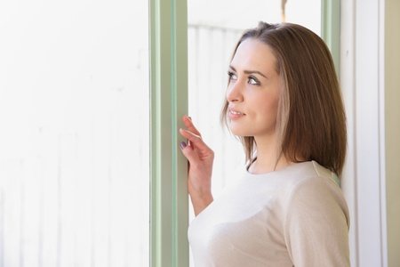 Beautiful caucasian woman standing by the window with space for copy photo