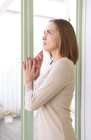 pelo castaño claro: Hermosa mujer de raza caucásica mirar por la ventana