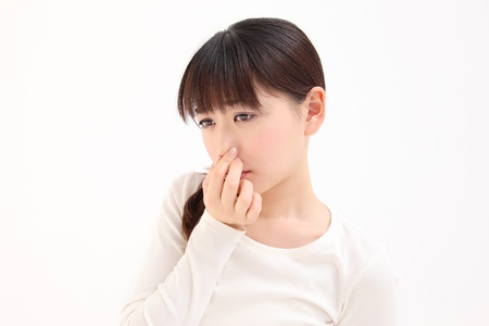 Young Asian woman pinch the nose white background Stock Photo