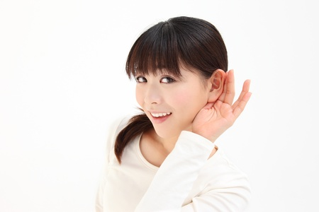Young Asian women devote to ear the hands of white background photo