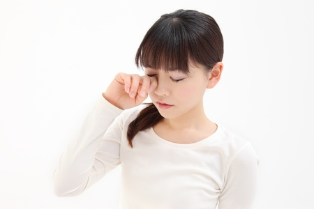 Young Asian woman touch the eye white background photo
