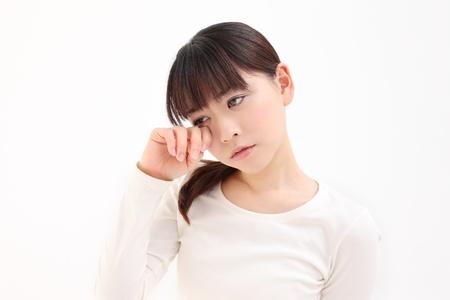 Junge asiatische Frau ber�hren das Auge wei�em Hintergrund Lizenzfreie Bilder