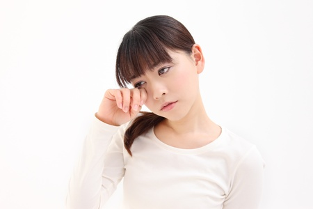Young Asian woman touch the eye white background Stock Photo