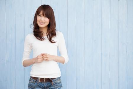 빈 공간과 파란색 배경 웃는 젊은 아시아 여자 스톡 콘텐츠