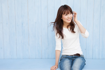 Der leere Raum in dem blauen Hintergrund der asiatischen Frauen und flatternden Haaren