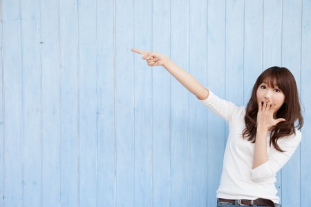 Young Asian woman pointing at a blue background photo