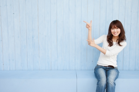 margins: Beautiful young Asian woman pointing with space for copy
