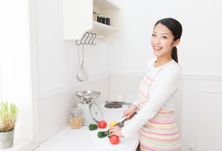 Asian woman cutting vegetables in the kitchen photo