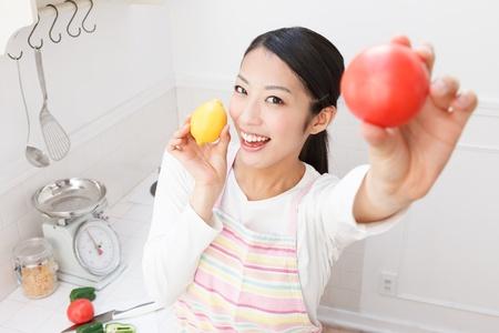 台所で野菜を持つ若いアジア女性